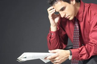 Business man reading stock quotes BE 2 - FAQ